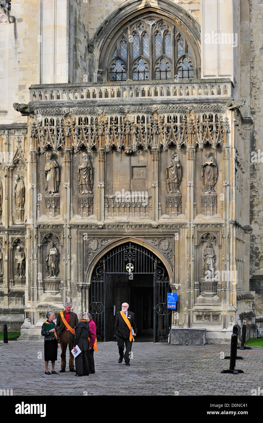 Tour guides wearing orange sashes leaving the Canterbury Cathedral in the medieval city Canterbury, Kent, England, - Stock Image