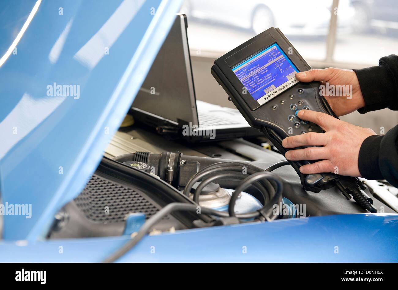 mechanic holding handheld diagnostics machine in garage workshop - Stock Image