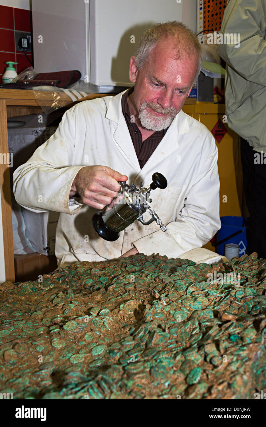 Neil Mahrer spraying water onto the Jersey Celtic coin hoard left by a Coriosolite tribe 50 BC, Jersey, Channel - Stock Image