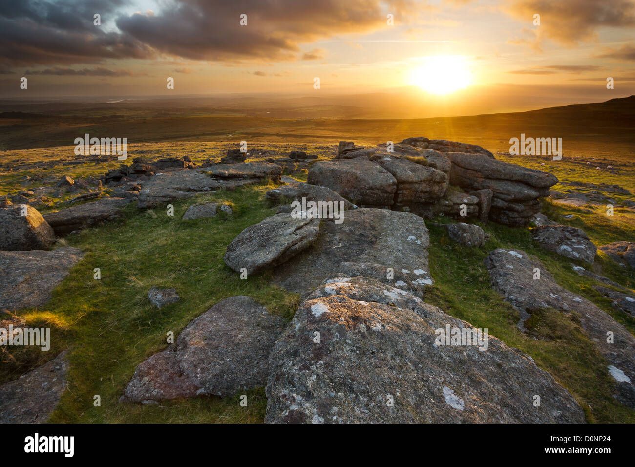 Sunset from Staple Tor casting a golden glow across the moorland looking towards Cox Tor. Dartmoor National Park, - Stock Image