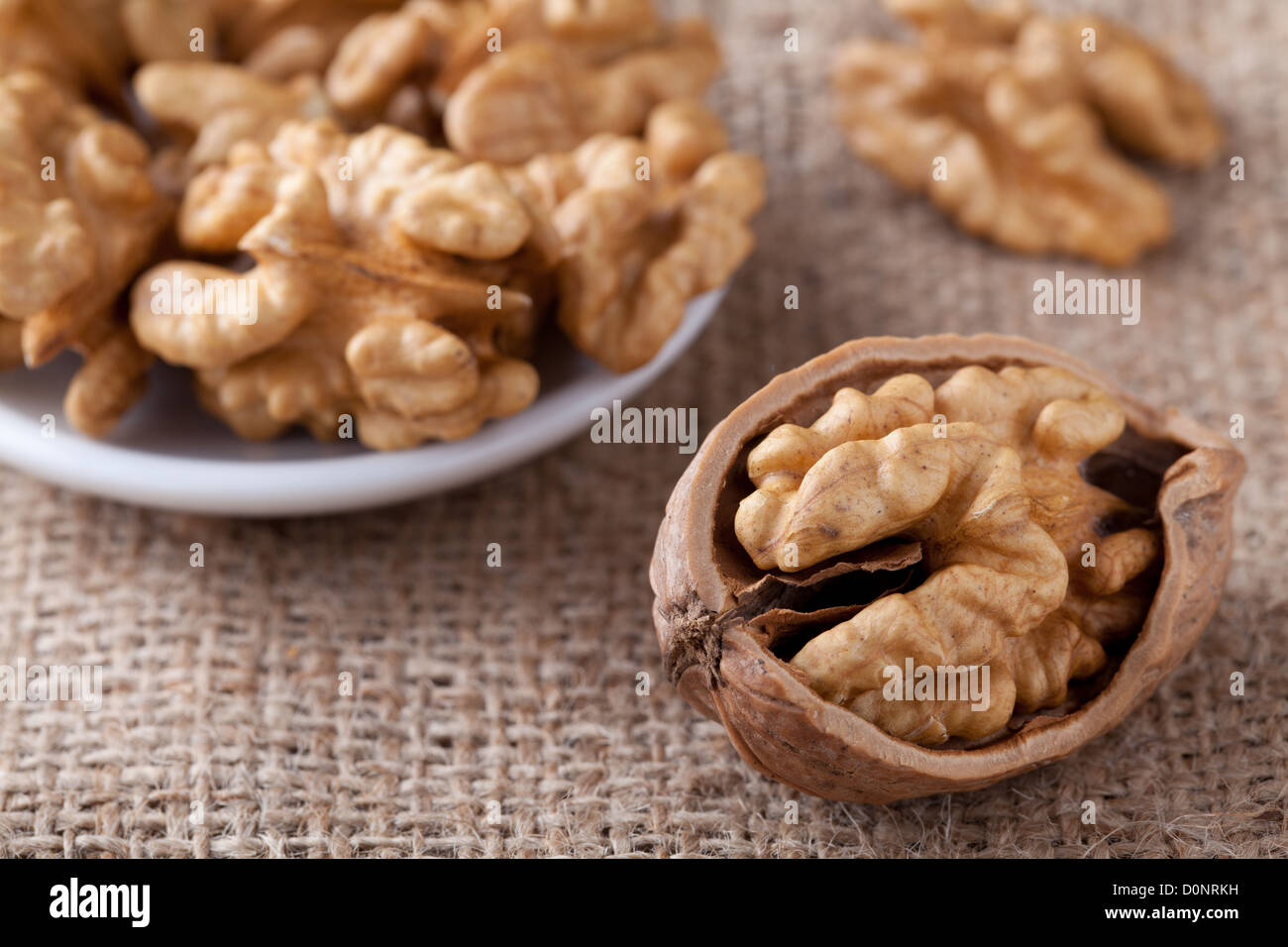 Cores of matured nuts in plate and cracked brown Circassian walnut close-up on the sackcloth background - Stock Image