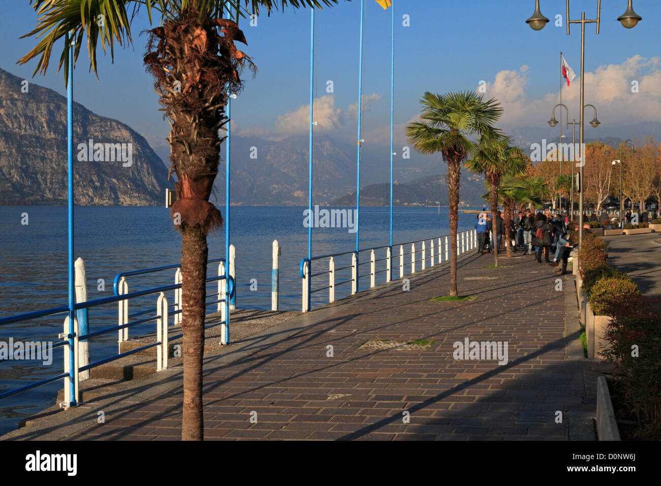 Tourists walking on the promenade by Lake Iseo near Bergamo in Autumn, Lombardy, Italy, Europe. - Stock Image