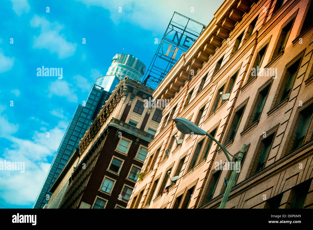 Old and sky scraper buildings in Downtown Los Angeles below a blue sky street lamp - Stock Image