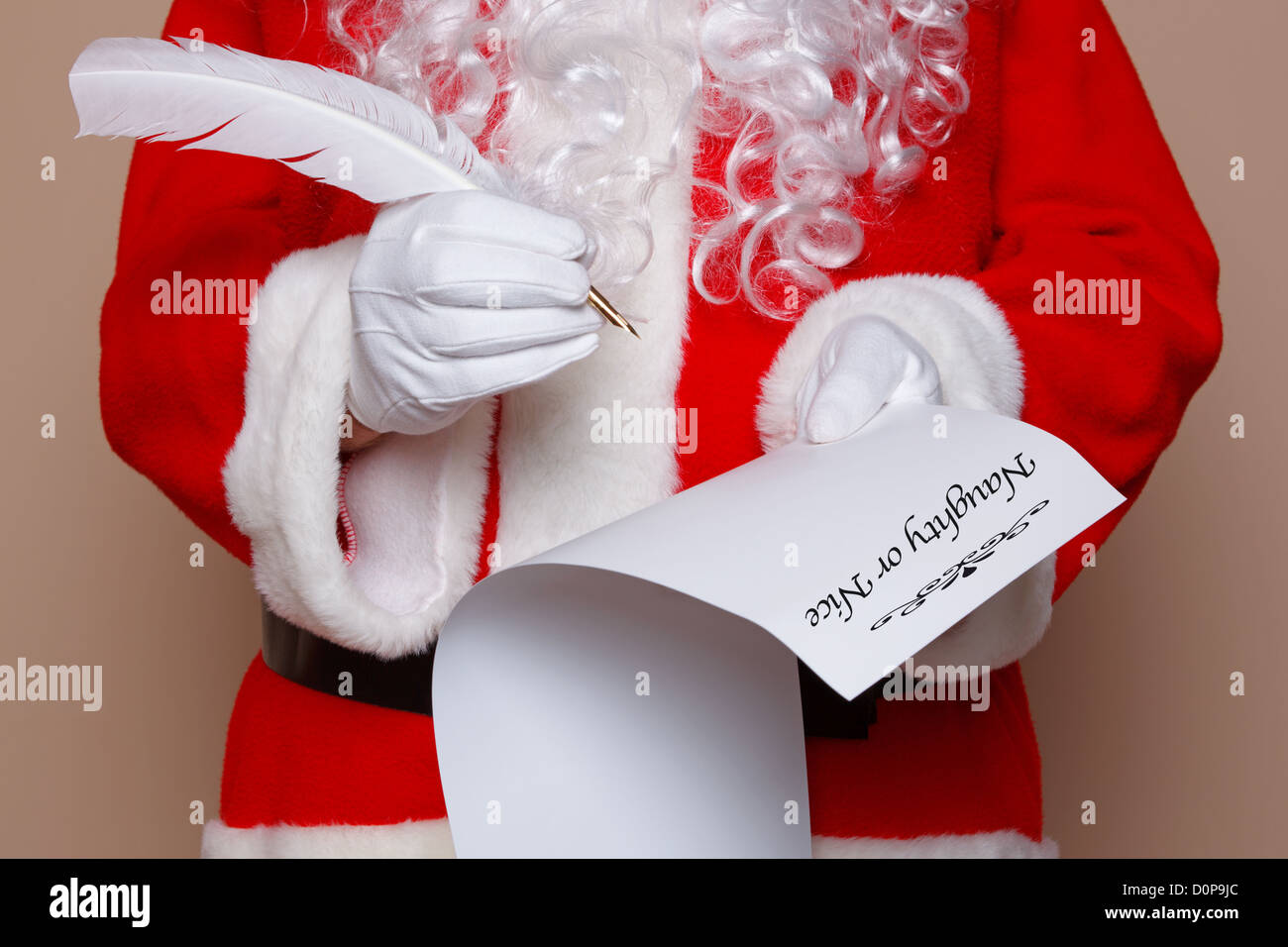 Santa Claus holding a quill pen whilst checking the naughty or nice list. - Stock Image