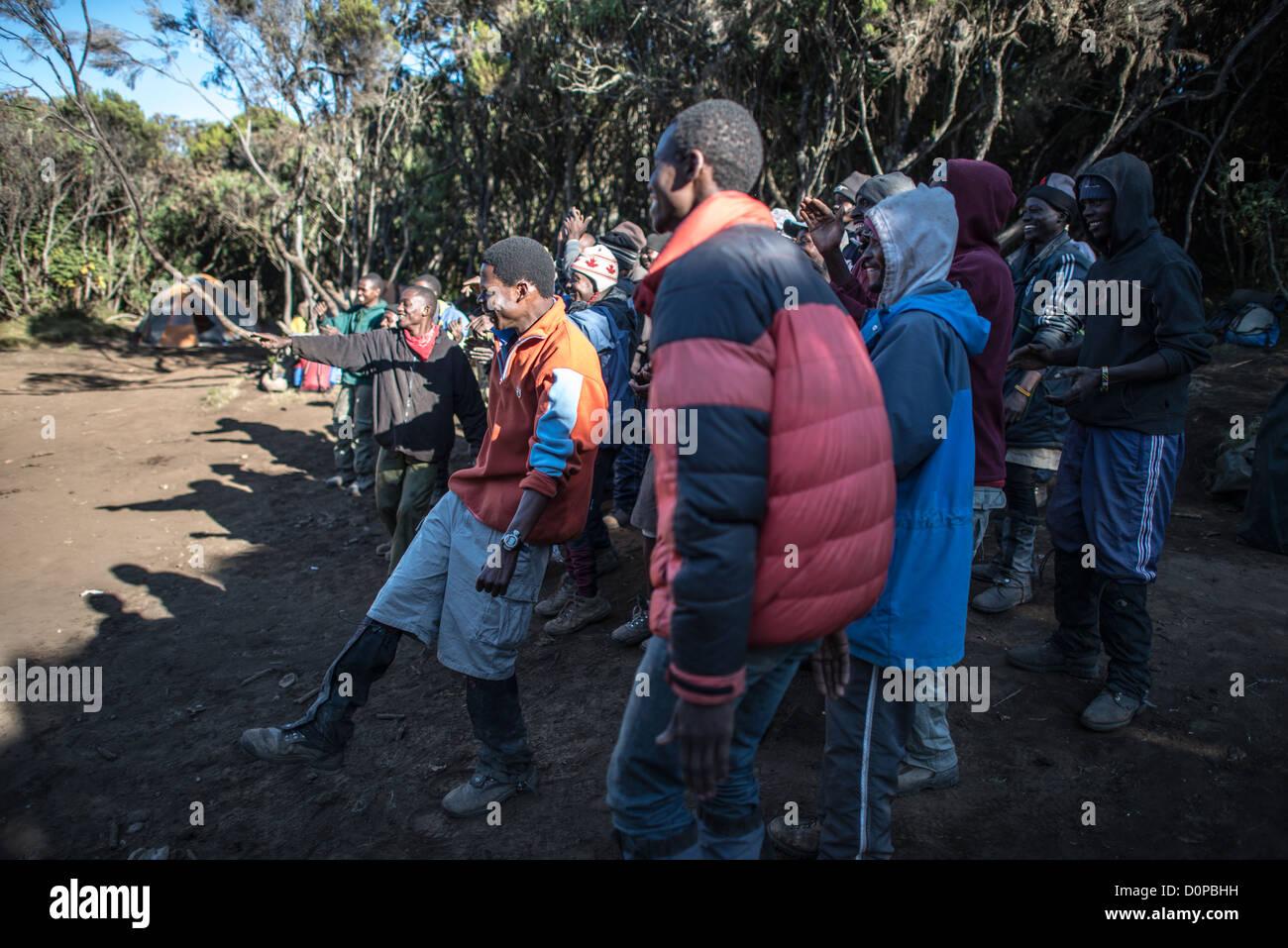 MT KILIMANJARO, Tanzania - Porters and guides sing the Kilimanjaro song as a group completes a climb of Mt Kilimanjaro - Stock Image