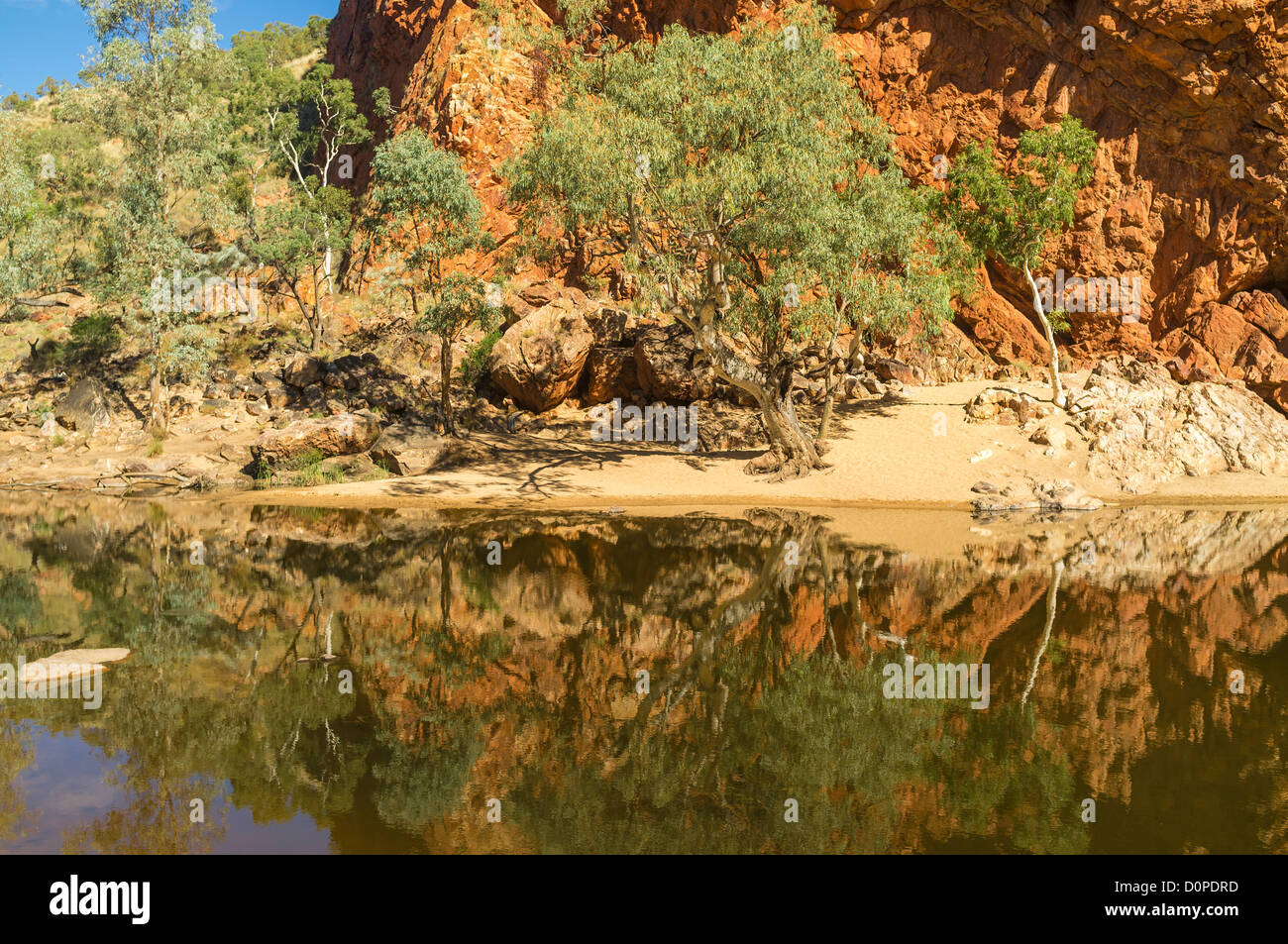 Red walls of Ormiston Gorge reflected in waterhole, West Macdonnell Ranges Ranges, Alice Springs, the Red Centre - Stock Image