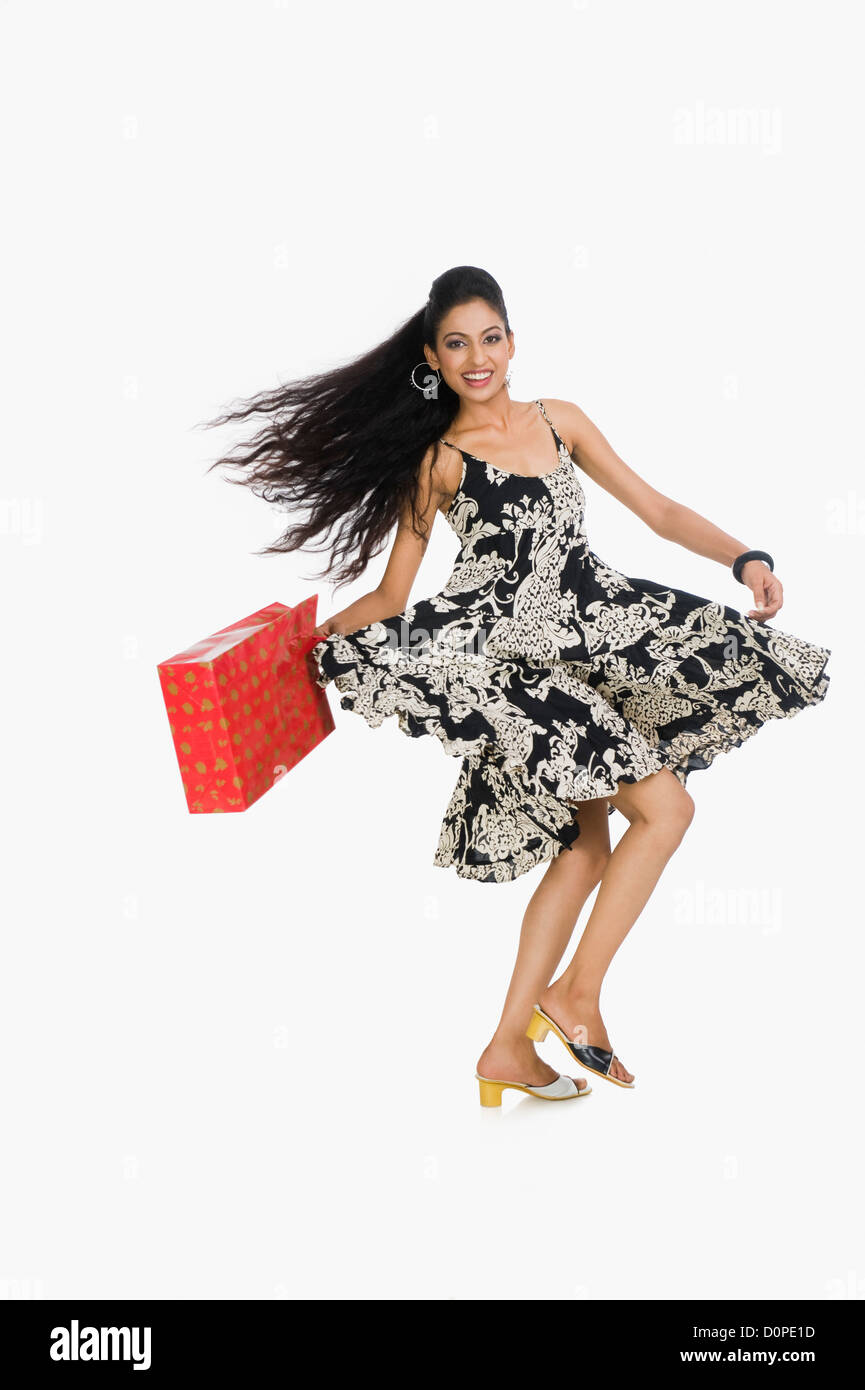 Woman carrying a shopping bag and dancing - Stock Image