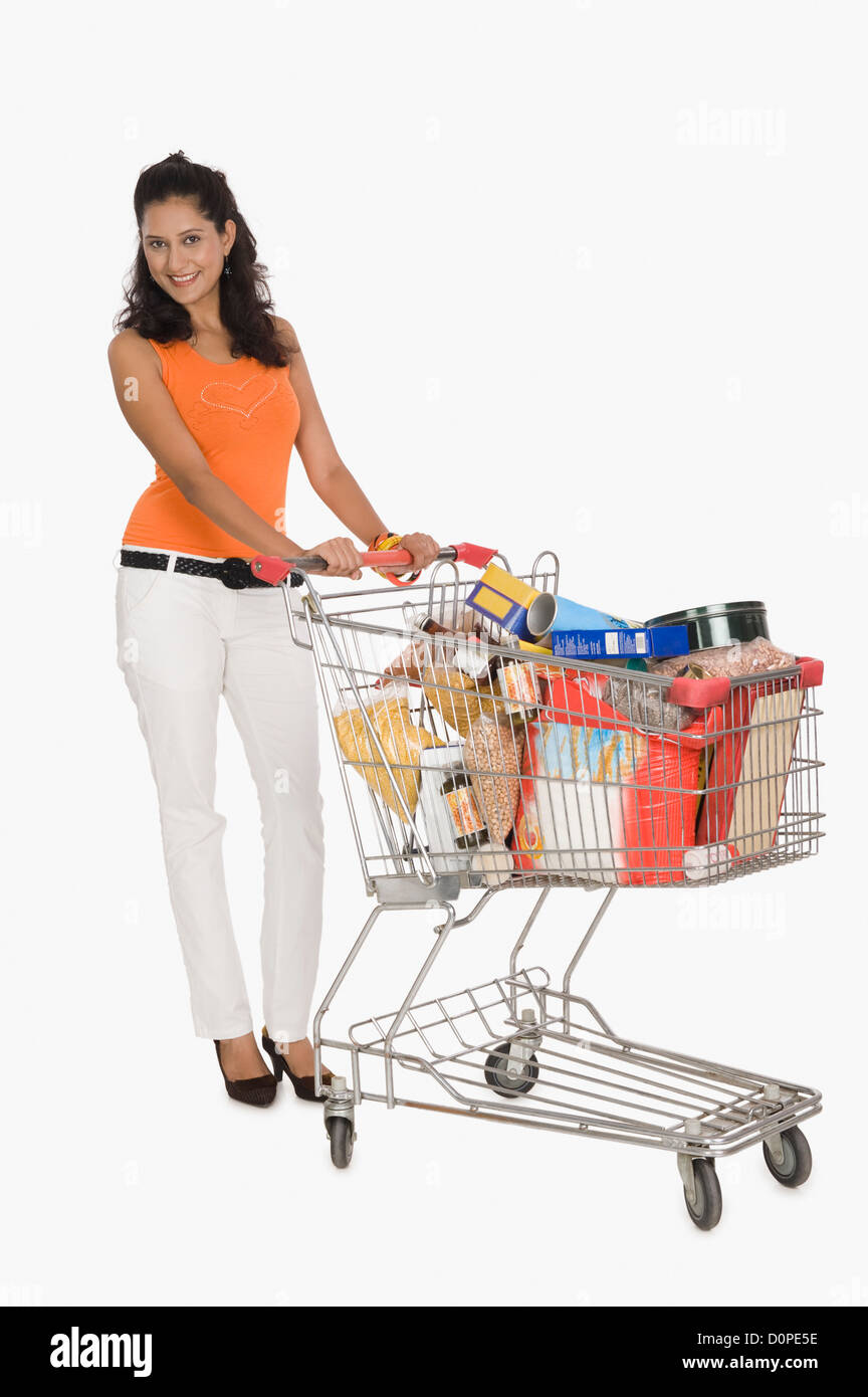 Portrait of a woman pushing a shopping cart - Stock Image