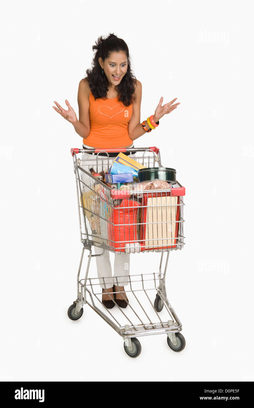 Woman looking at a shopping cart and surprised - Stock Image