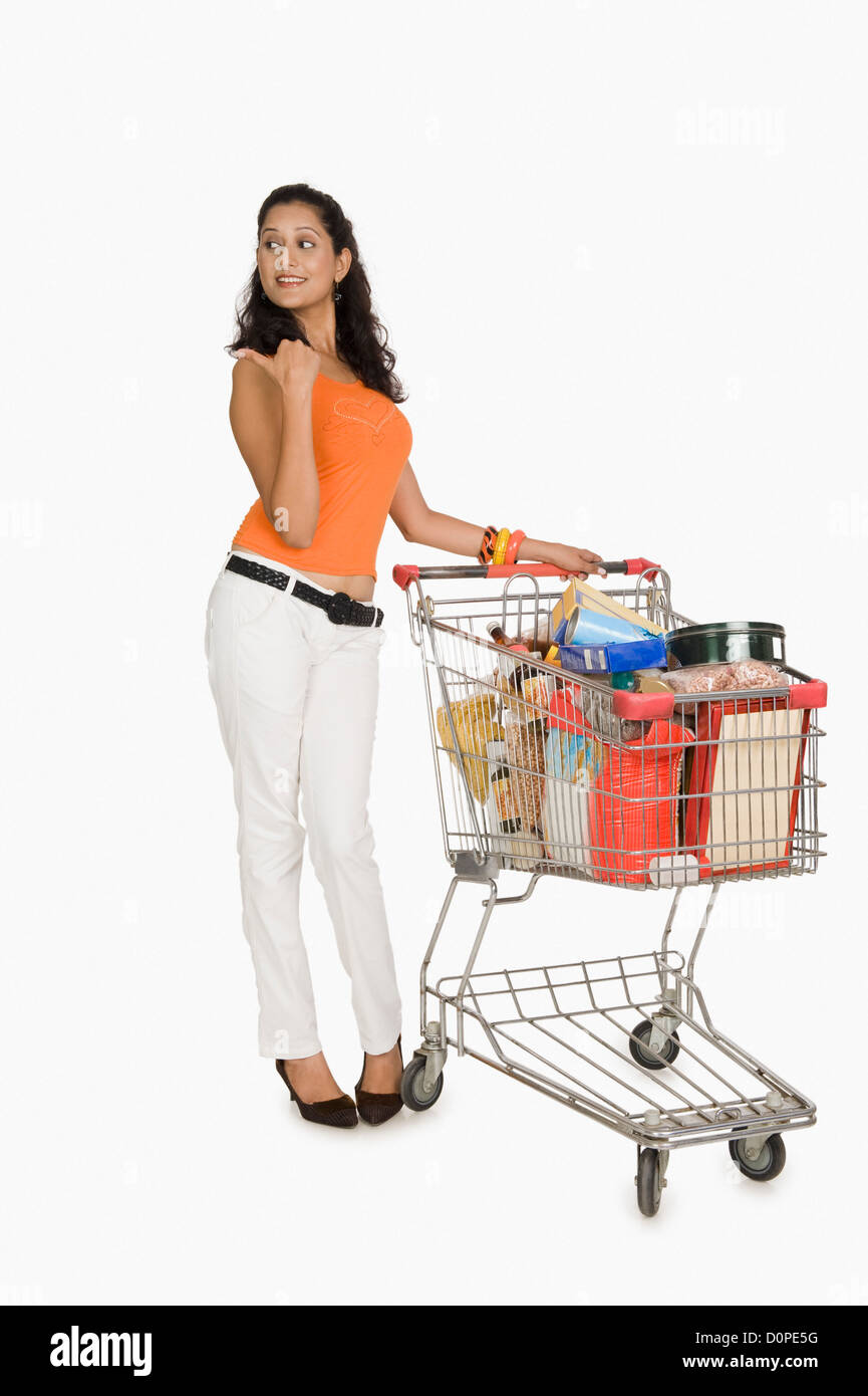 Woman standing with a shopping cart and pointing - Stock Image