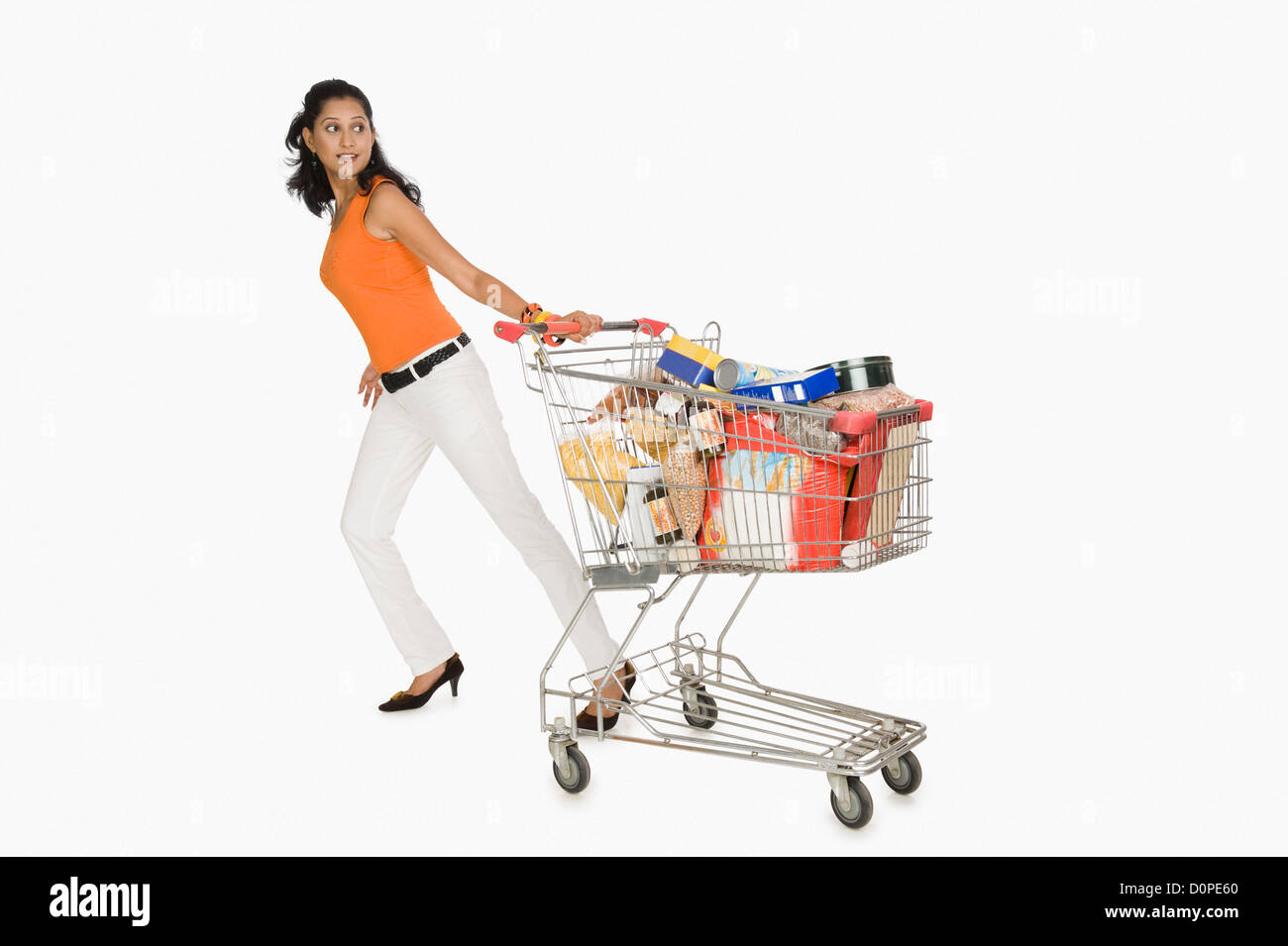 Woman pulling a shopping cart and smiling - Stock Image