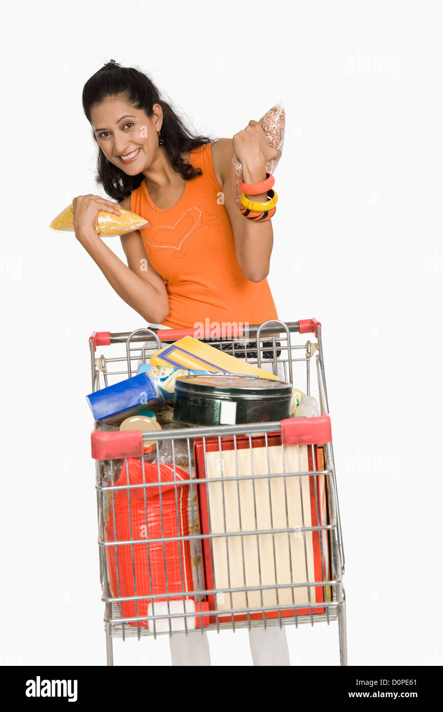 Woman standing with a shopping cart and smiling - Stock Image
