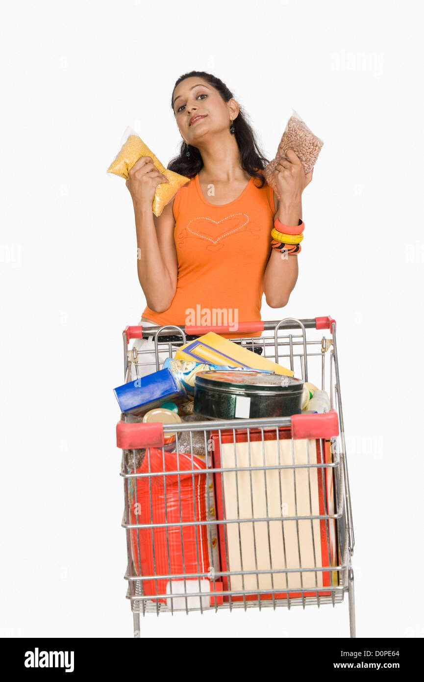 Woman standing with a shopping cart and showing packets - Stock Image