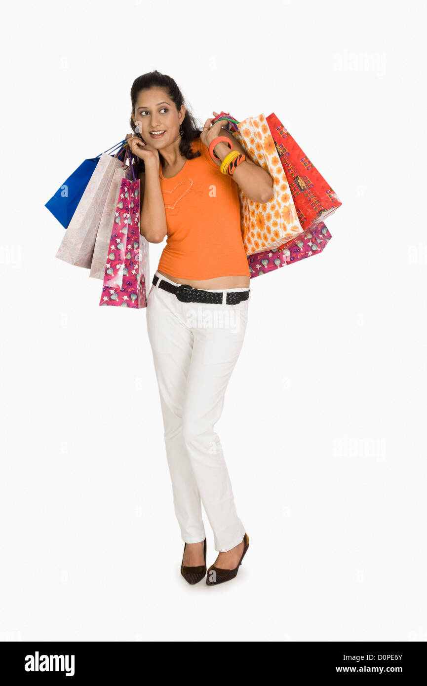 Woman carrying shopping bags and looking afraid - Stock Image