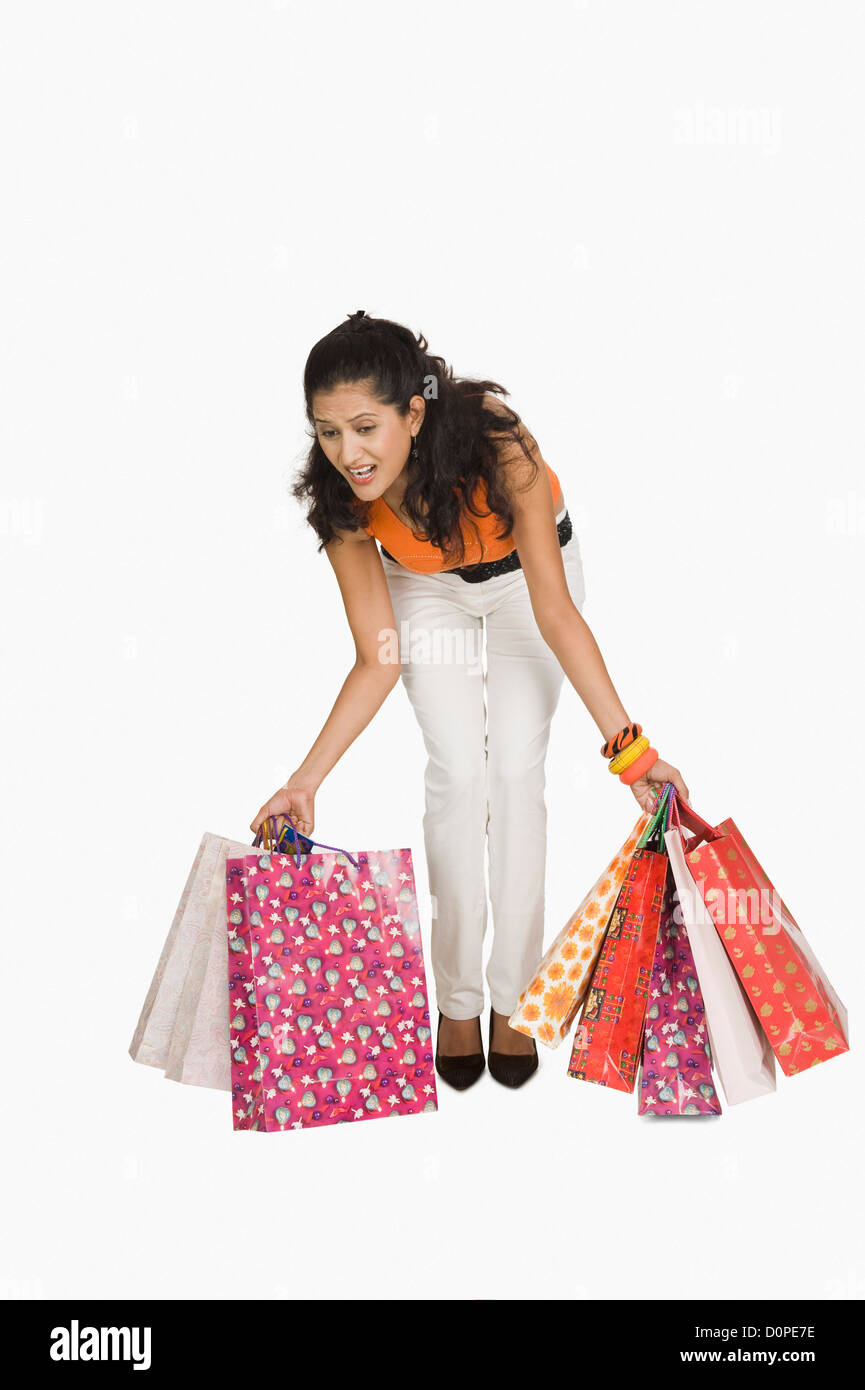 Woman trying to lift shopping bags - Stock Image