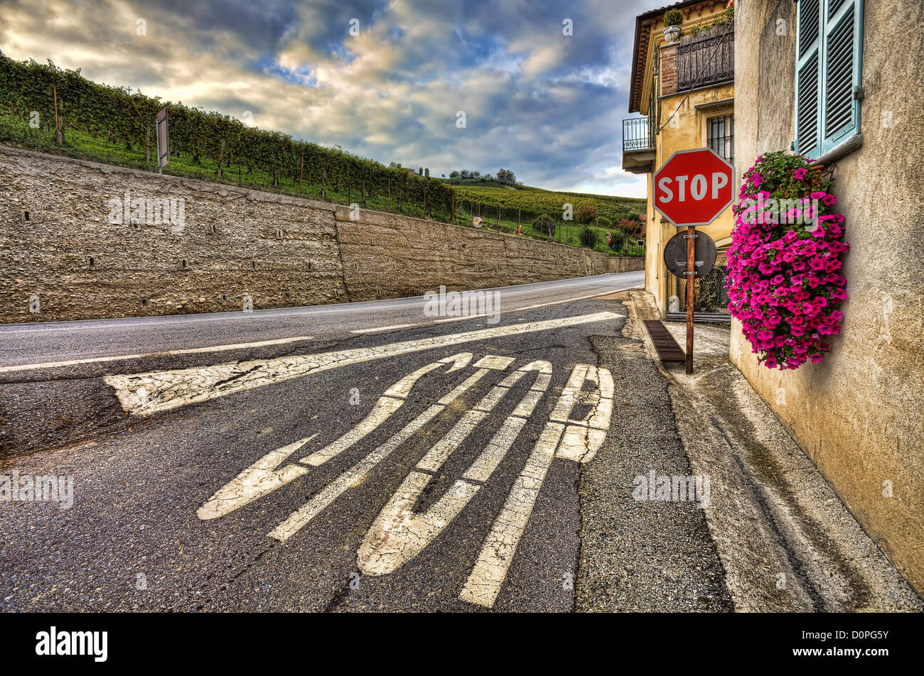 Stop sign on the narrow road among old house and vineyards under cloudy sky in Piedmont, Northern Italy. - Stock Image