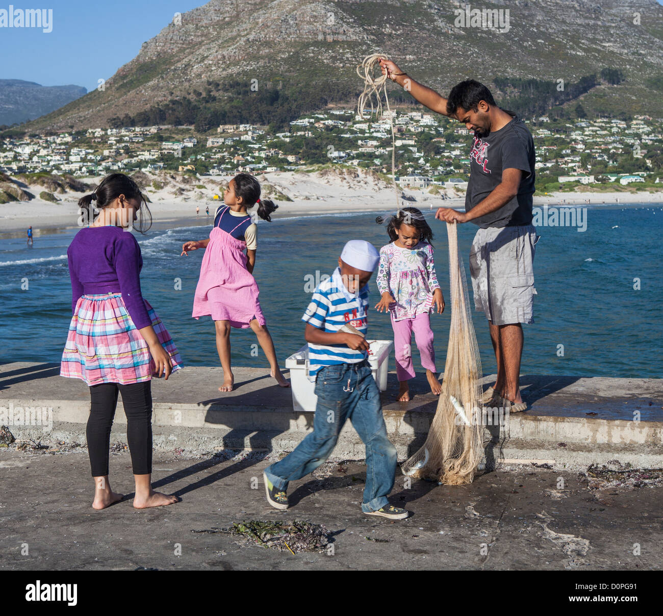 A father retrieves a fishing net and his children help with the catch after a sardine run - Hout Bay harbour, Western - Stock Image