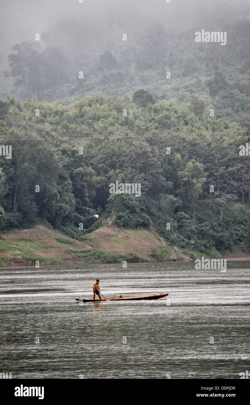 NONG KHIAW, Laos - A man paddles his wooden fishing canoe on the Nam Ou (River Ou) in Nong Khiaw in northern Laos. - Stock Image