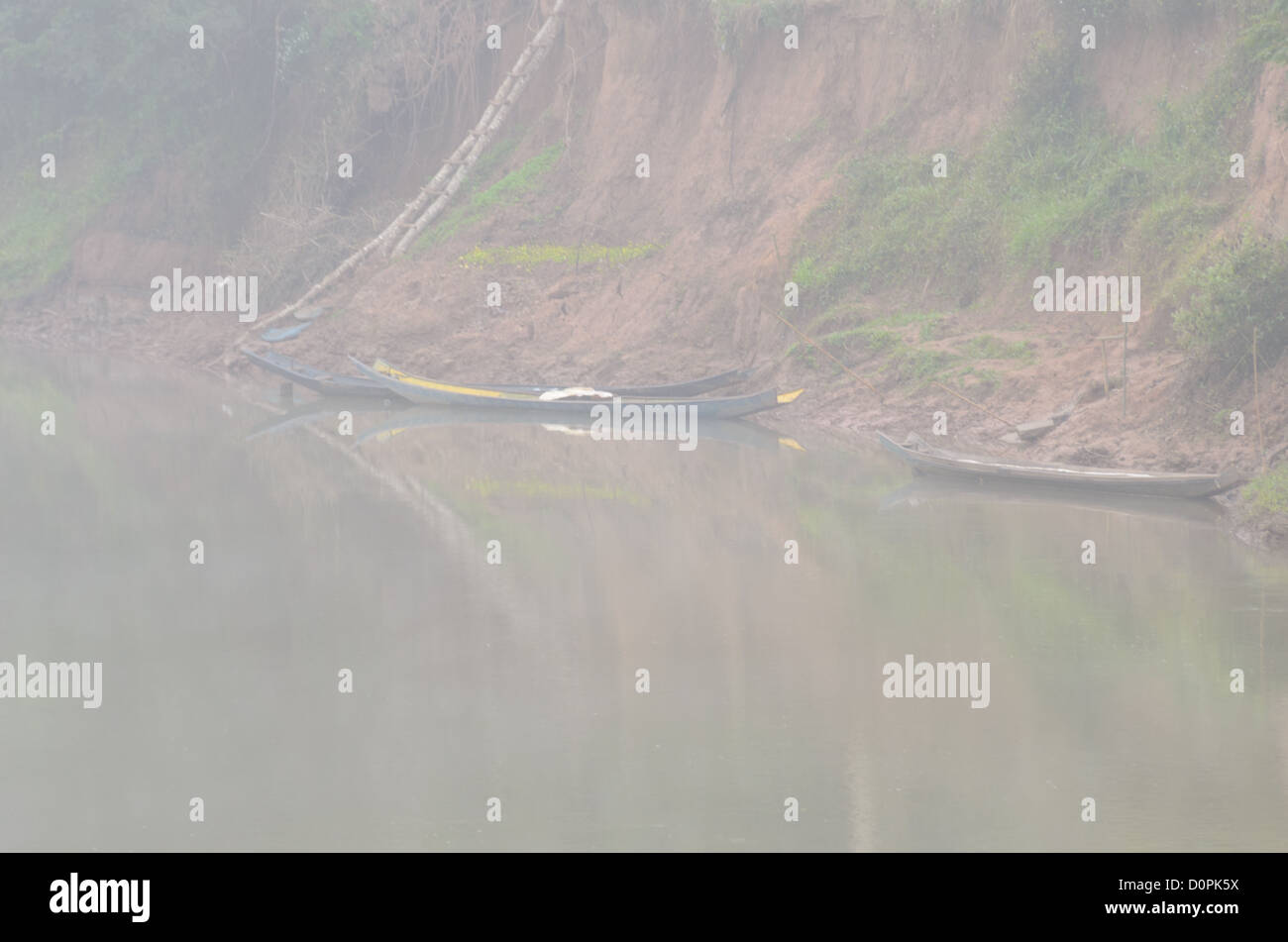 LUANG NAMTHA, Laos - Morning mists shroud and wooden boats on the shore of the River Tha (Nam Tha) in Luang Namtha - Stock Image