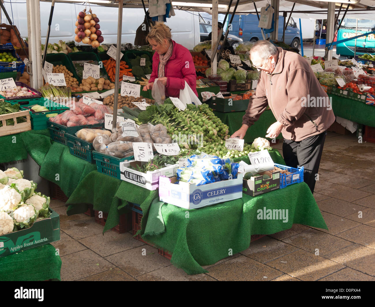 Man and woman serving themselves with vegetables at the twice weekly Market Day in Northallerton North Yorkshire - Stock Image