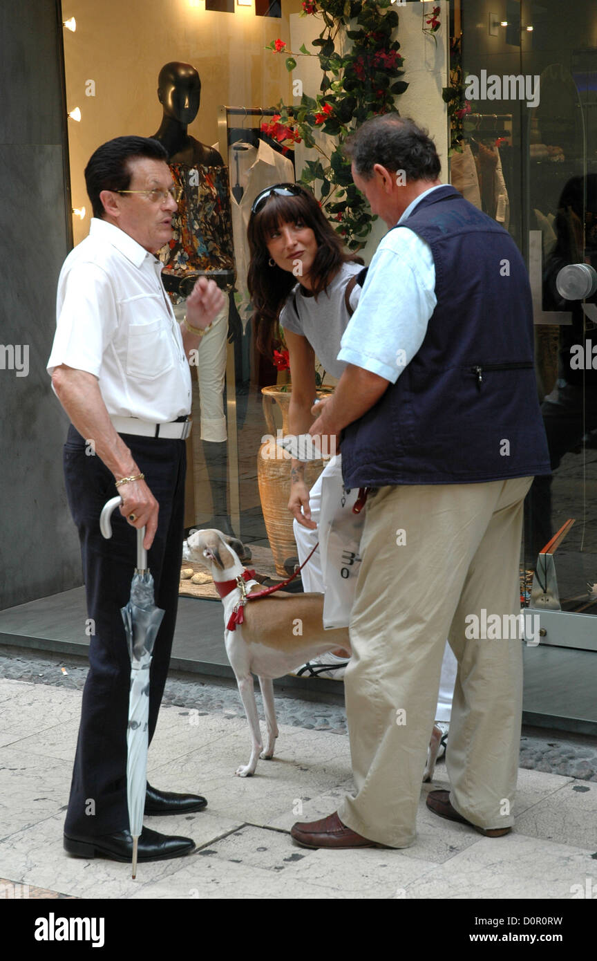 Italy -Two gentlemen of Verona chat in the street with a lady and her dog - Stock Image
