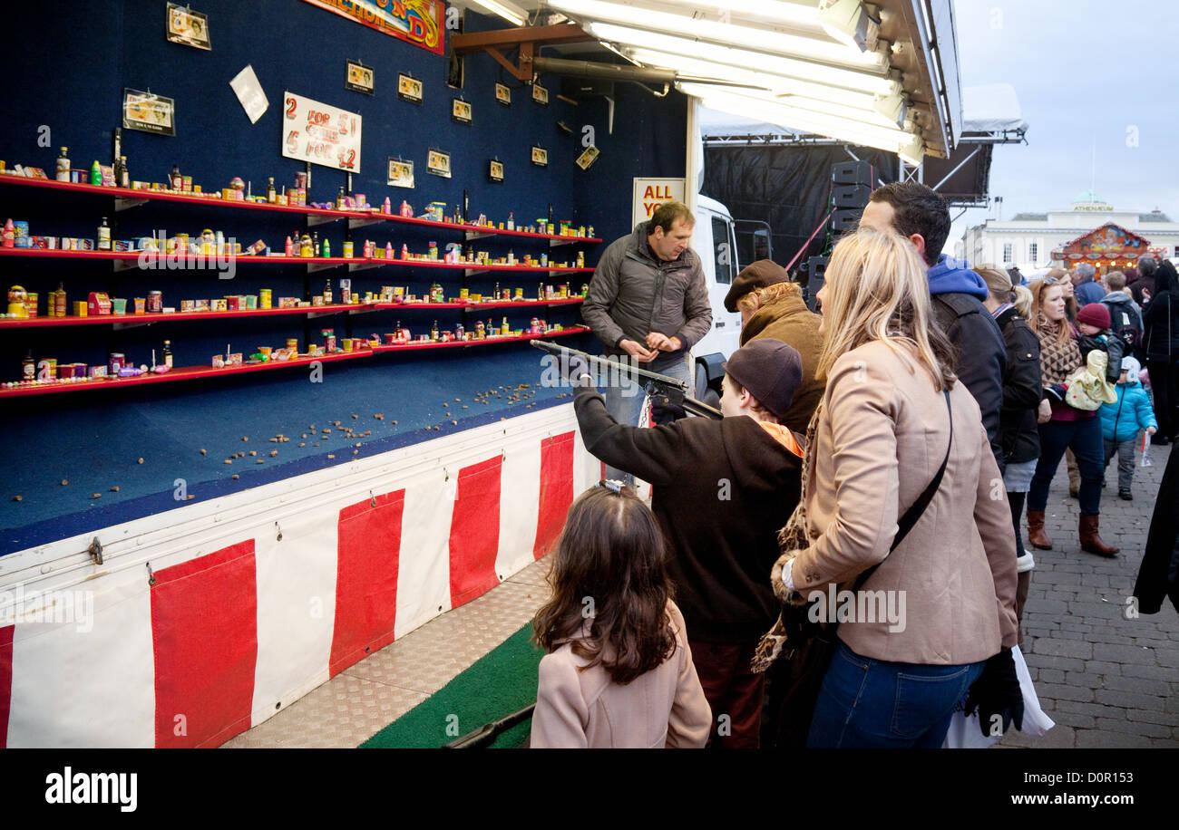 Fairground game child rifle shooting with family, Bury St Edmunds Christmas market fair, Suffolk UK - Stock Image