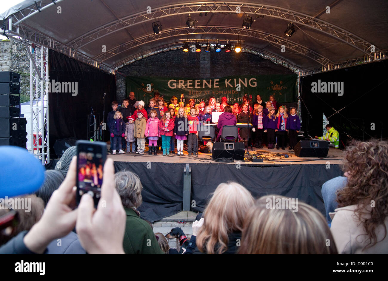 Primary School children singing on stage in public, Bury St Edmunds Christmas market, Suffolk England UK - Stock Image