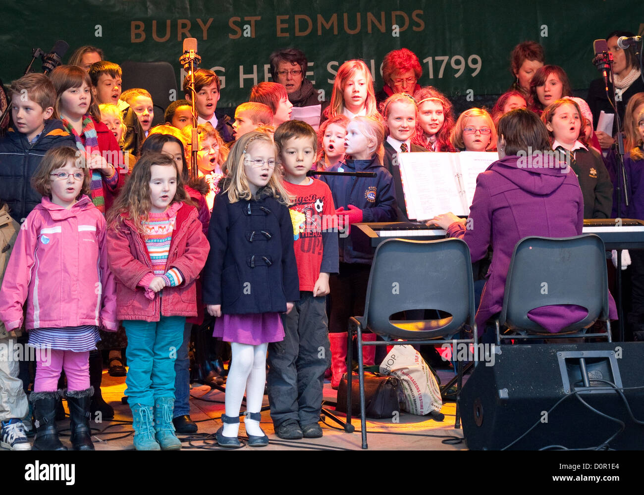 Children singing in a primary school choir, on stage at the Christmas market, Bury St Edmunds, Suffolk UK - Stock Image