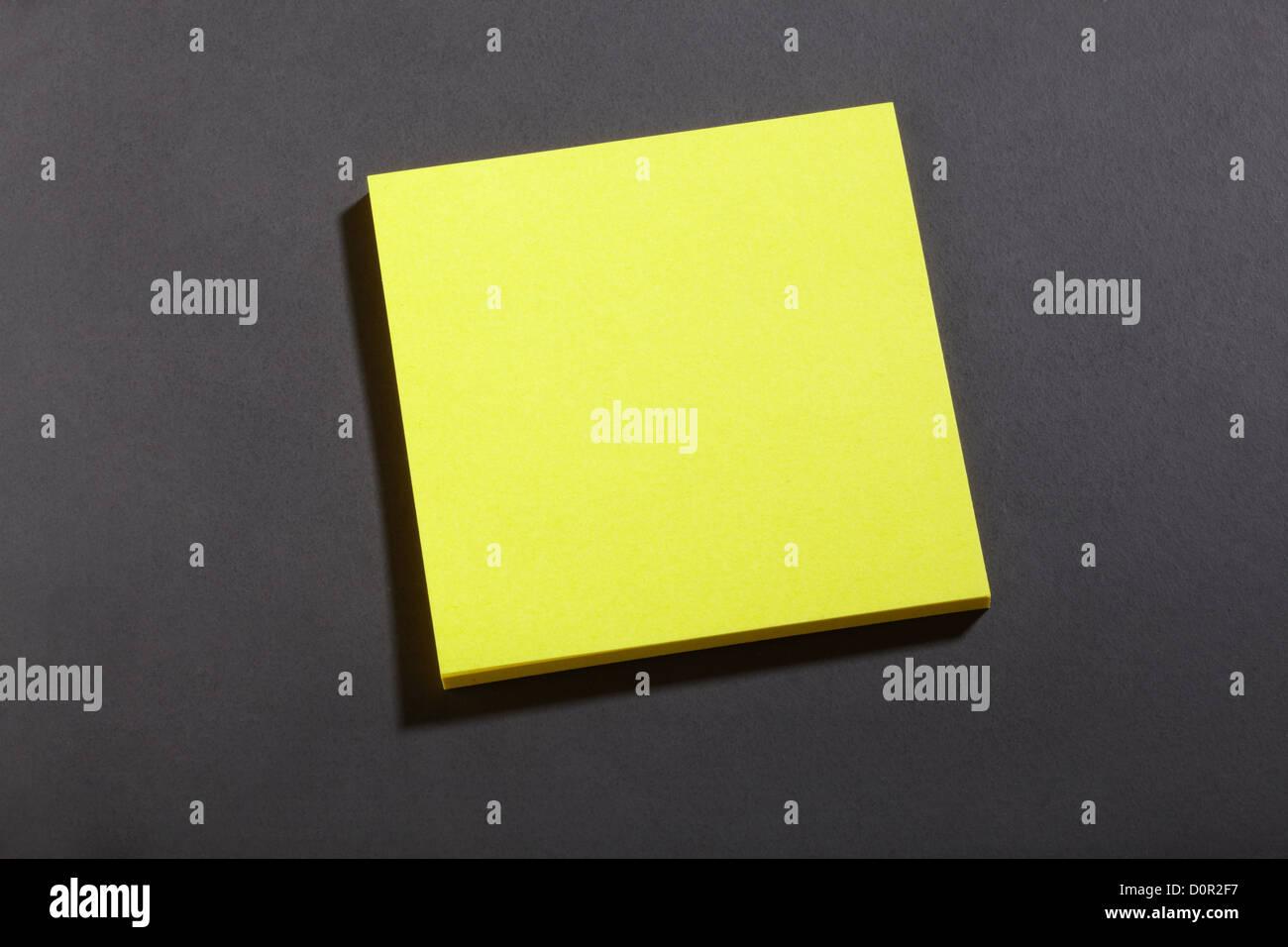 Yellow sticker note on blackboard - Stock Image