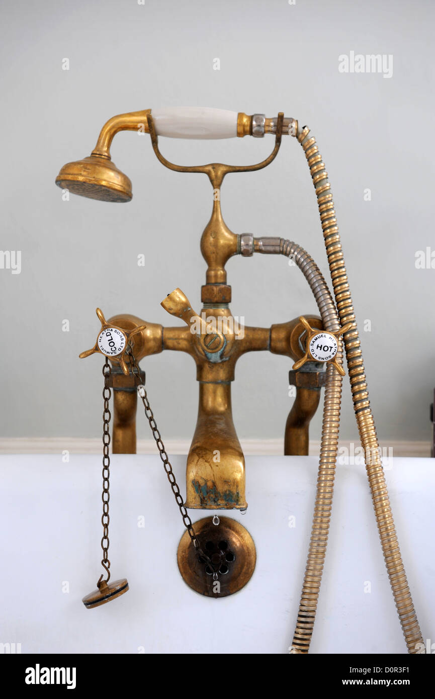 An antique brass mixer tap and shower head on a bath UK Stock Photo ...
