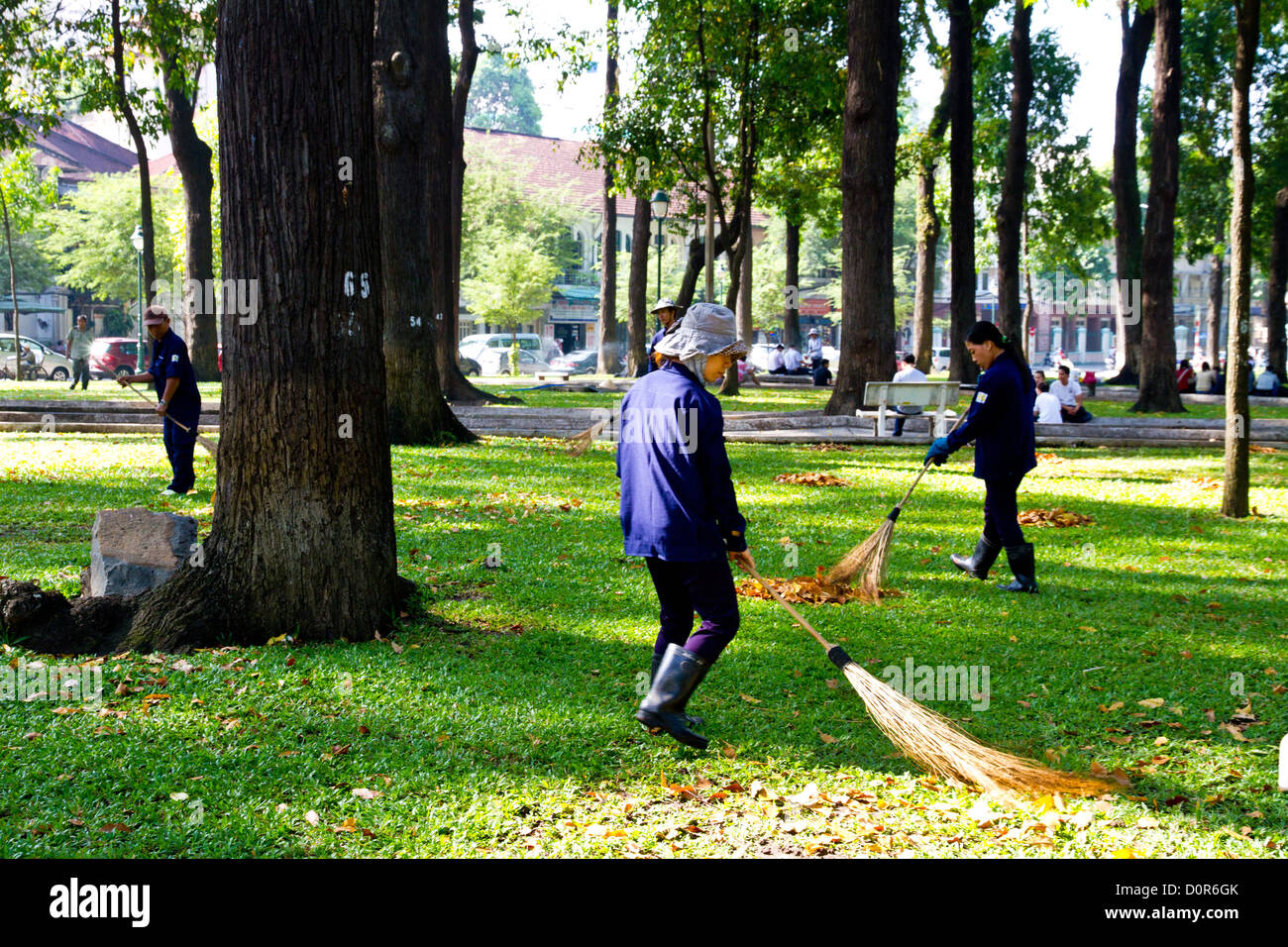 Workers sweeping up leaves in Ho Chi Minh City in Vietnam. - Stock Image