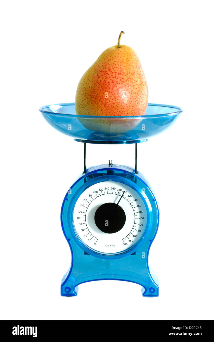 Pear on kitchen scale - Stock Image