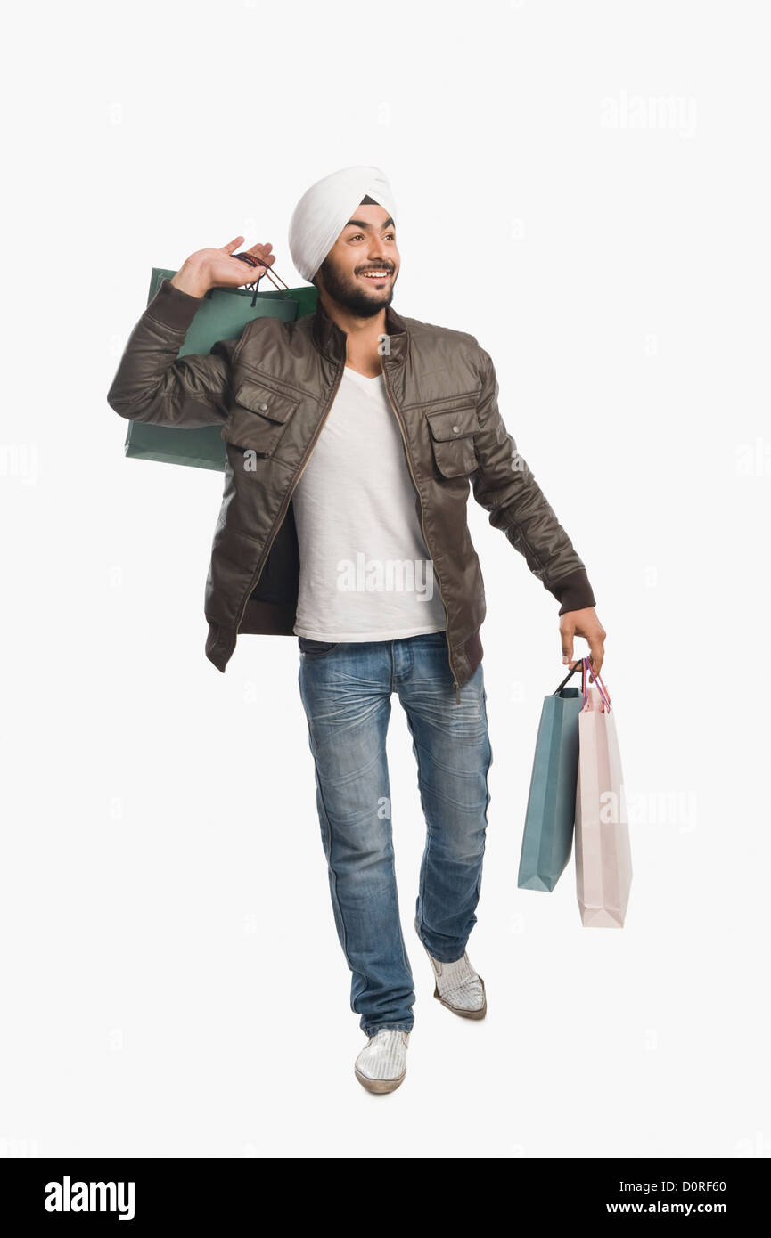 Man carrying shopping bags and smiling - Stock Image