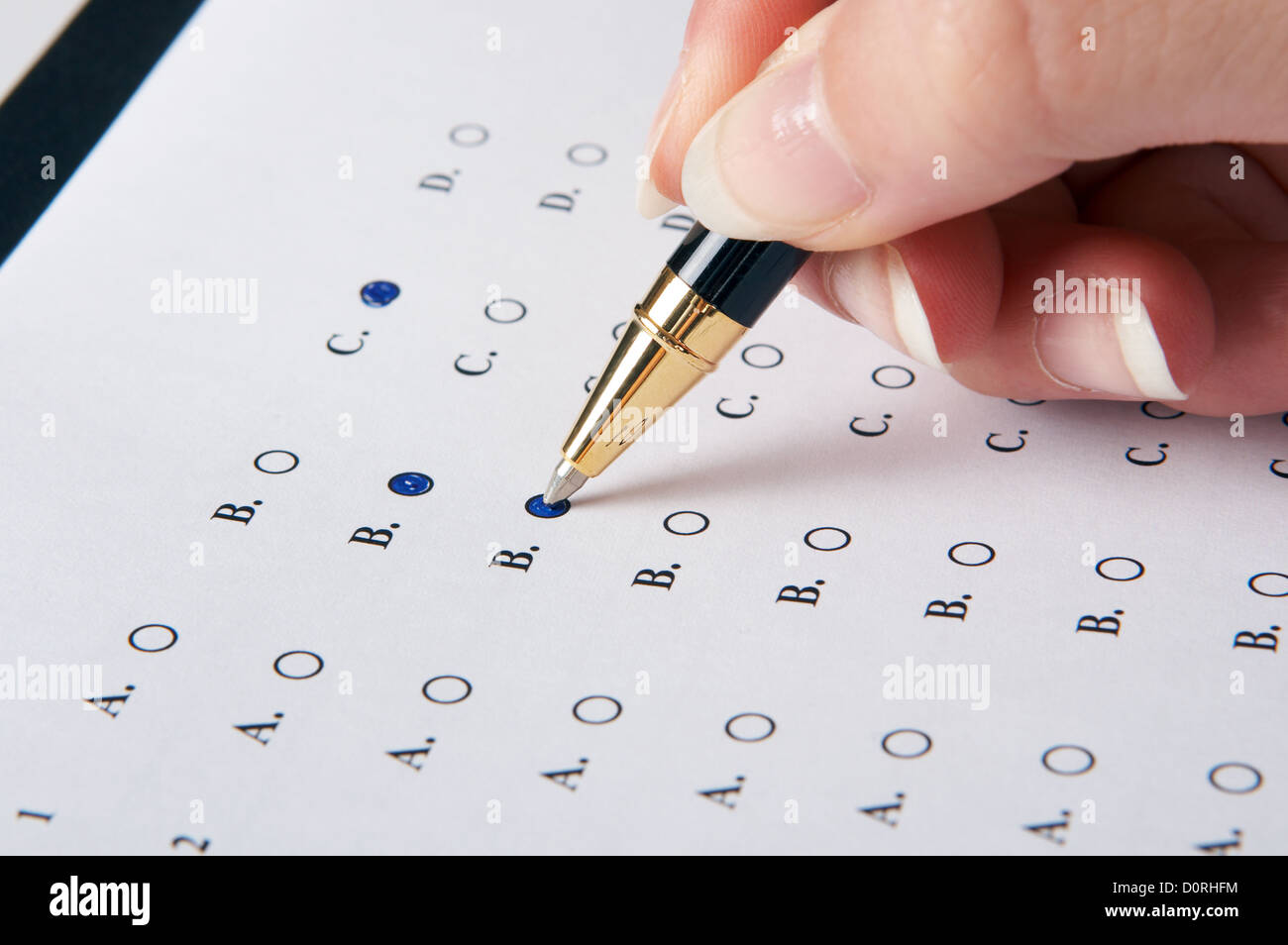 Hand filling in an evaluation form with a pen - Stock Image