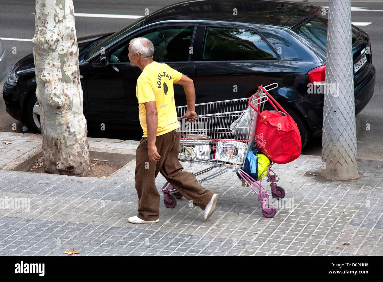 Man collecting scrap metal in supermarket trolley. - Stock Image