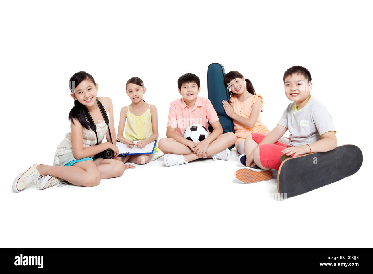 Merry children sitting on the floor and their leisure hobbies - Stock Image