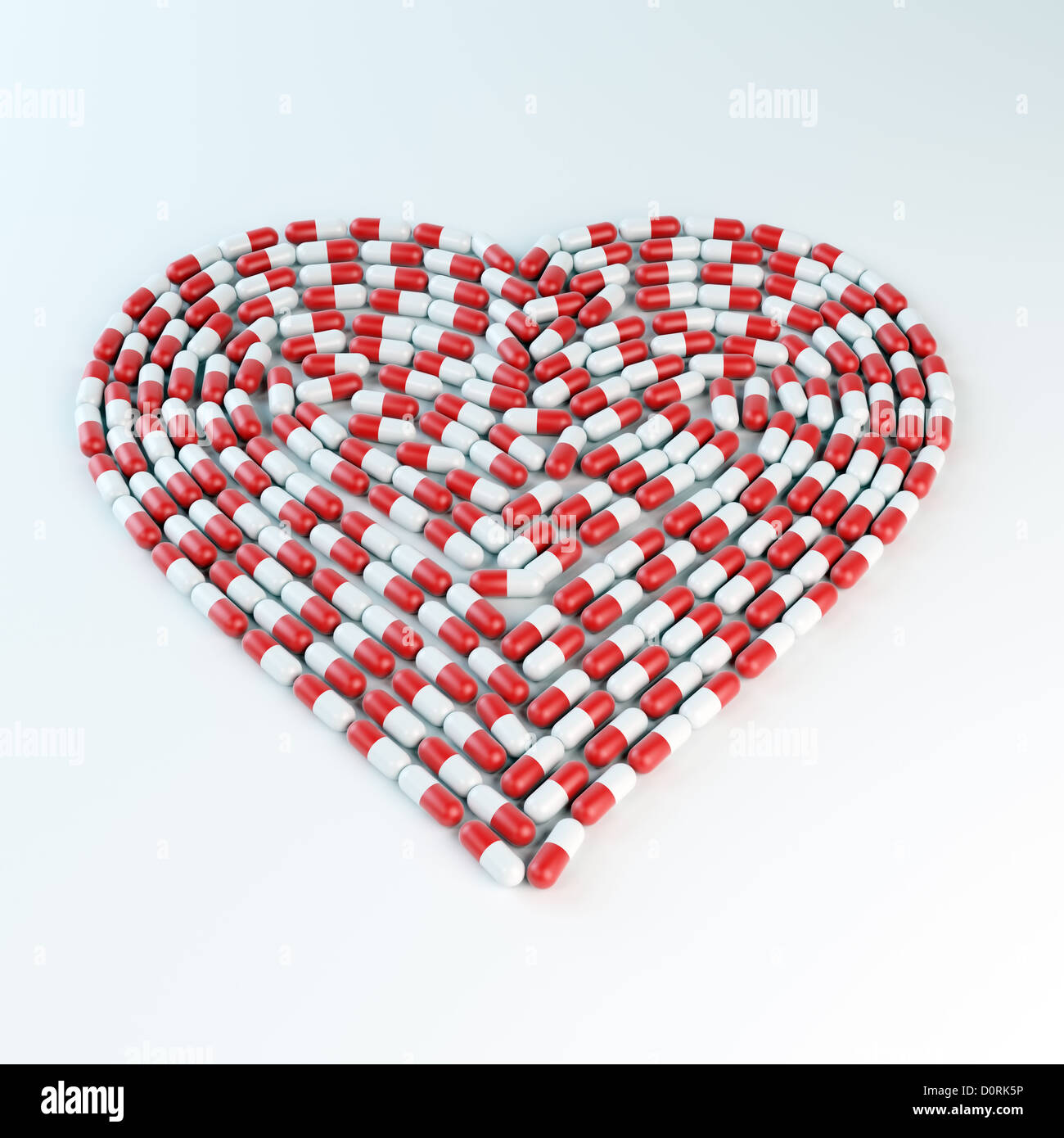 Red and white capsules forming a heart shap - Stock Image