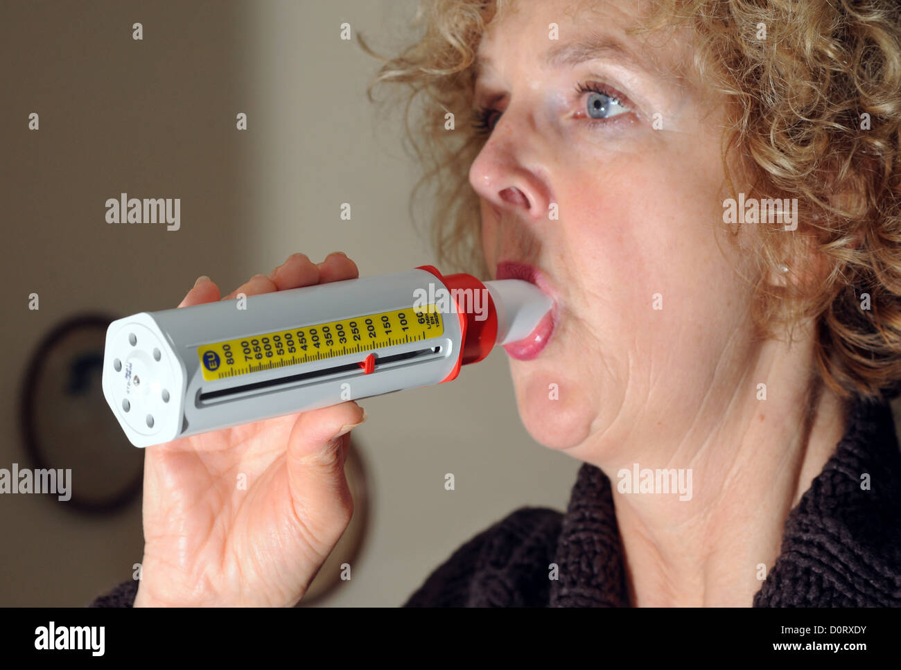 Middle aged female asthma sufferer blowing into a peak flow meter tester . - Stock Image