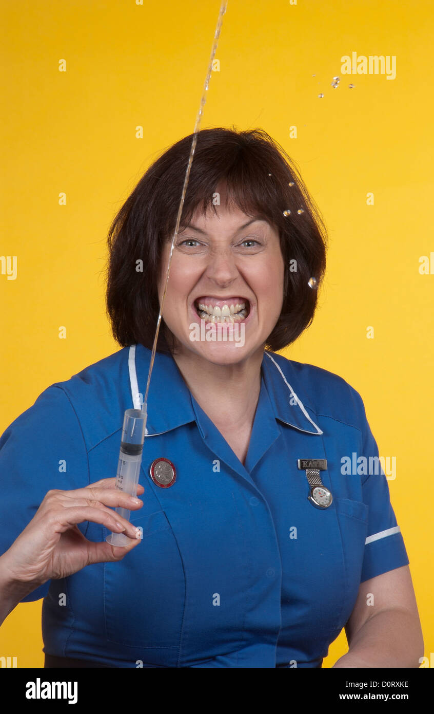 Portrait of a nurse baring her teeth and squirting a syringe. - Stock Image
