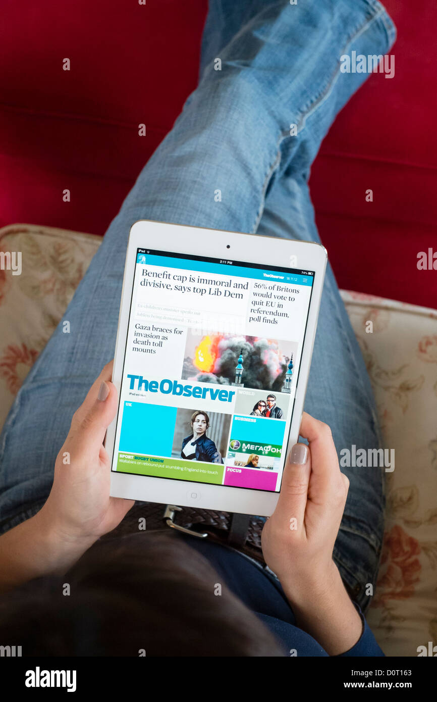 Woman using Kindle application of read digital edition of The  Observer newspaper  on an iPad mini tablet computer - Stock Image