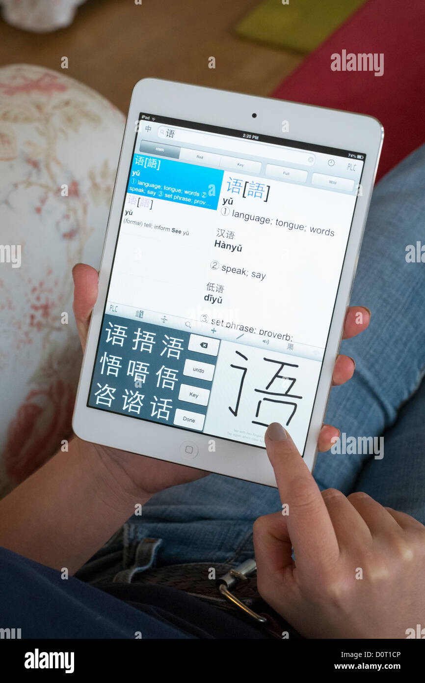 Student using iPad mini to learn Mandarin Chinese foreign language using educational application - Stock Image