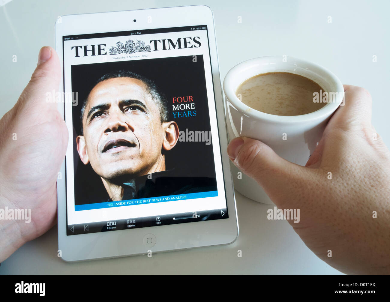 Using an iPad mini tablet computer to read The Times digital newspaper edition - Stock Image