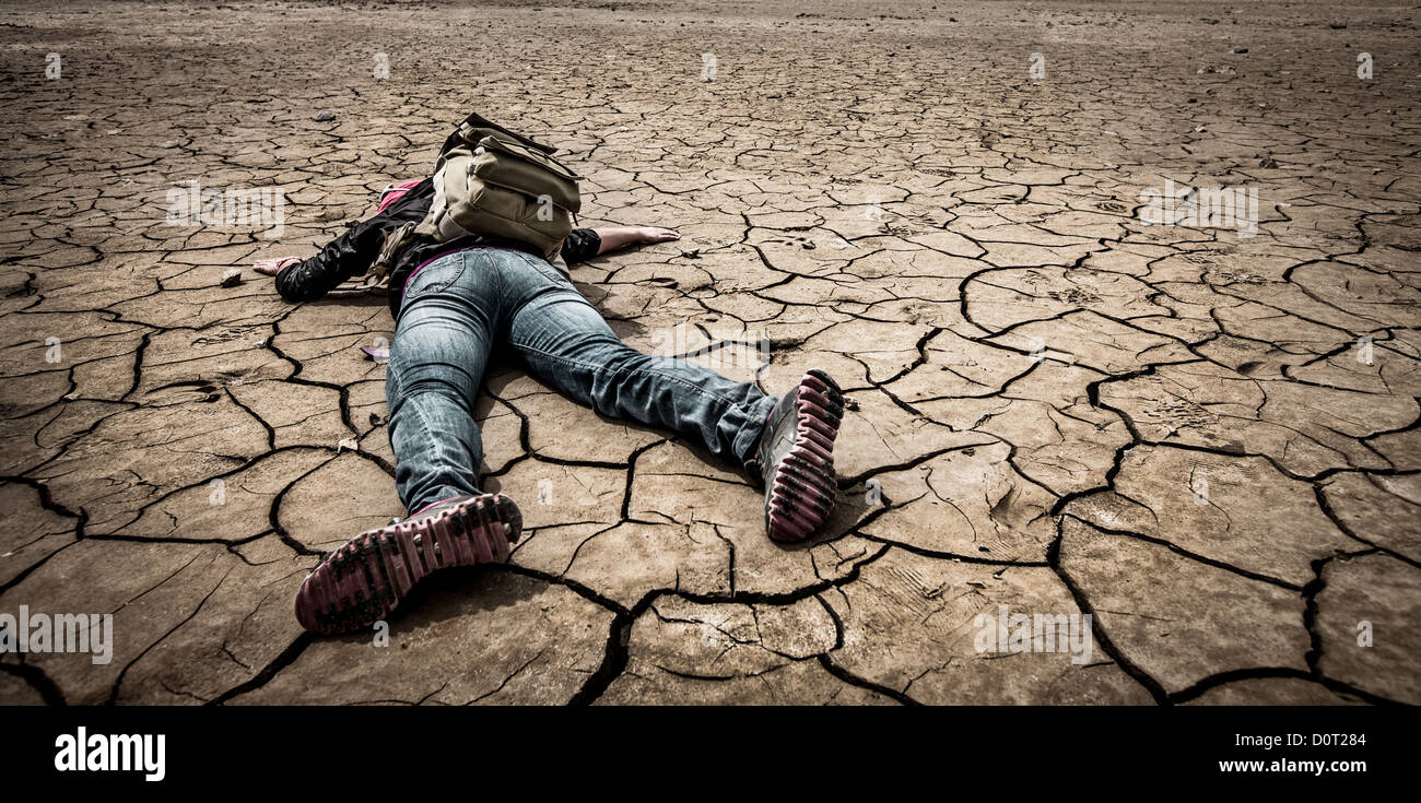 person lays on the dried ground - Stock Image