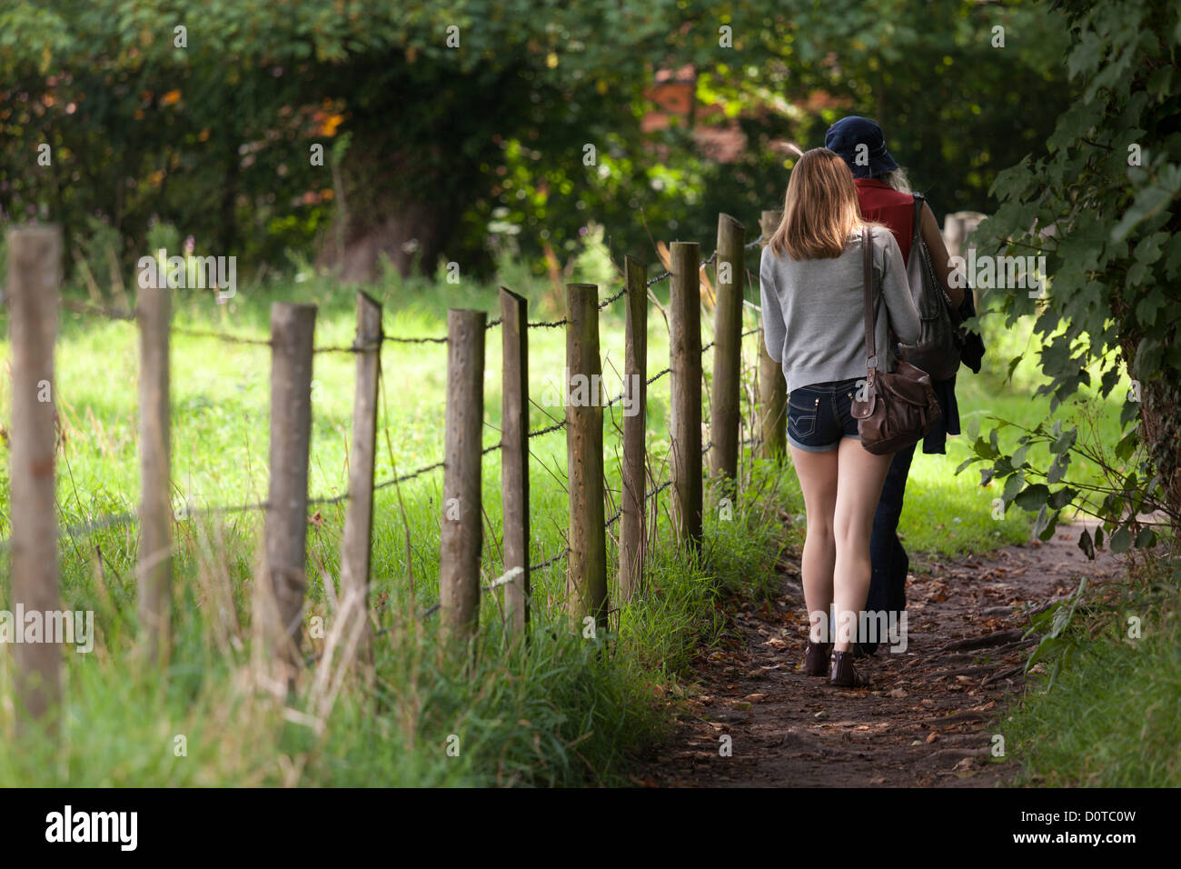 back to camera girl and woman walking on country footpath alongside post and wire fence - Stock Image