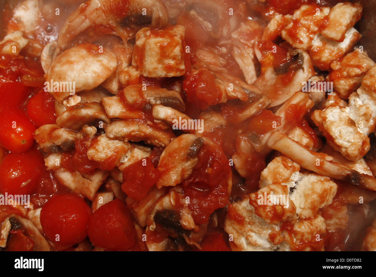 chopped tomatoes, mushrooms and quorn chicken pieces cooking in a pan - Stock Image