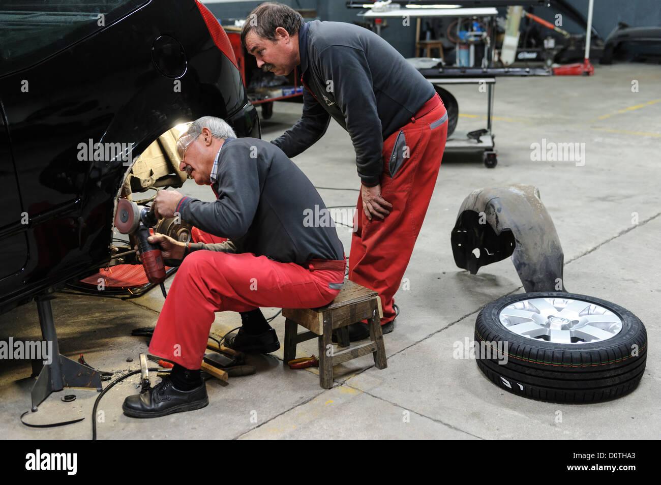 Two mechanics working in auto garage - Stock Image