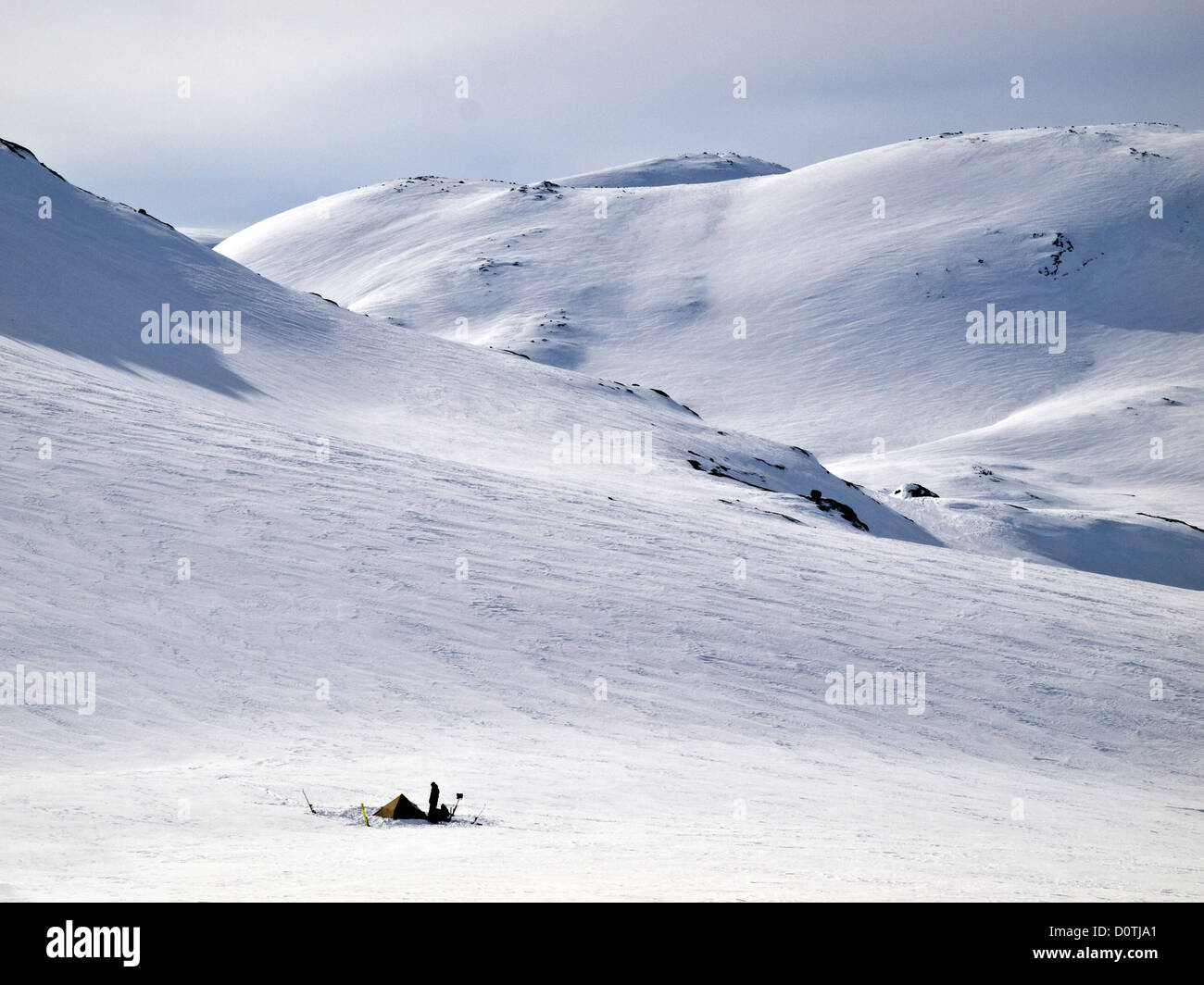 Figure stood by a tent in snowy wilderness, Hardanger ,Norway - Stock Image
