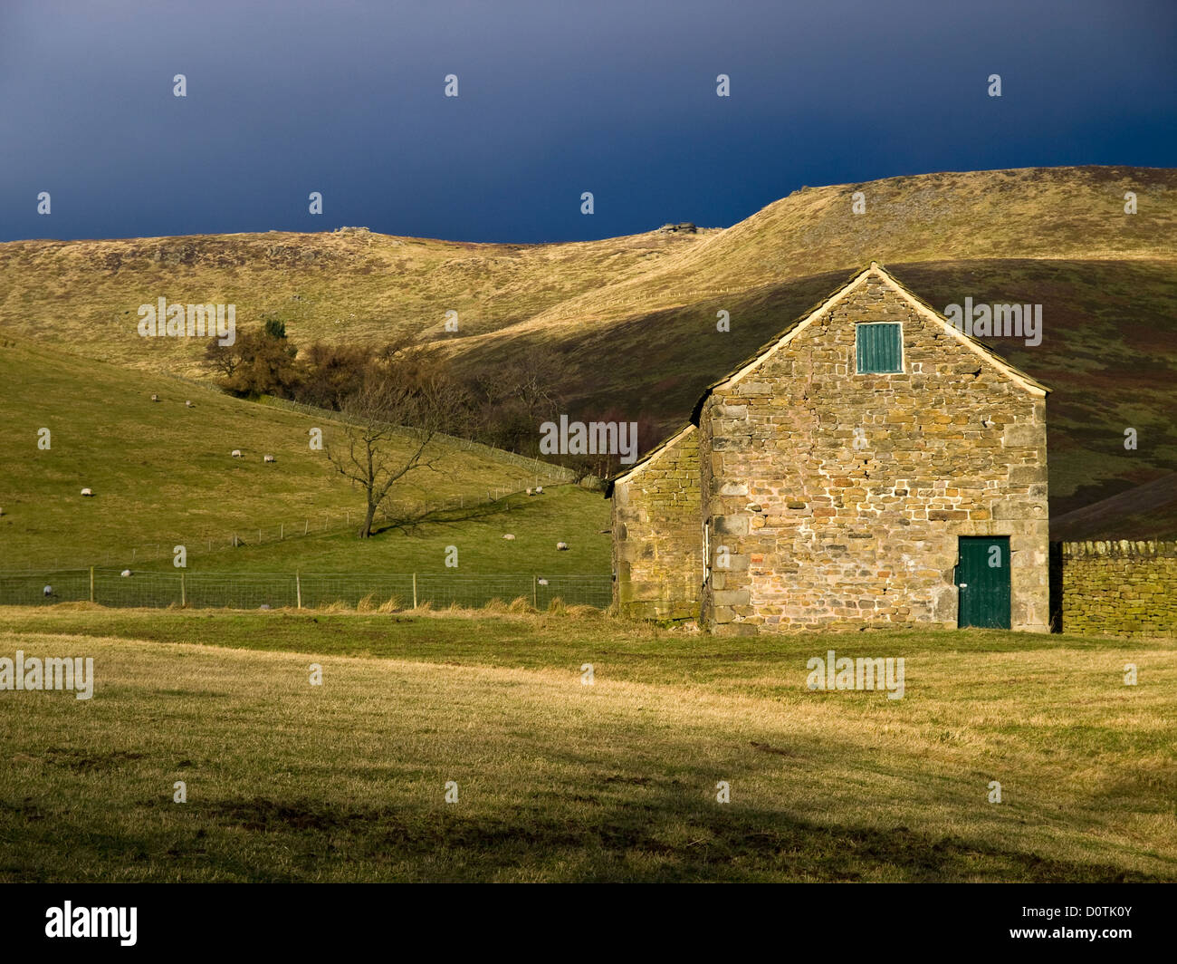 A barn below The southern edge of Kinder Scout, Peak District National Park - Stock Image