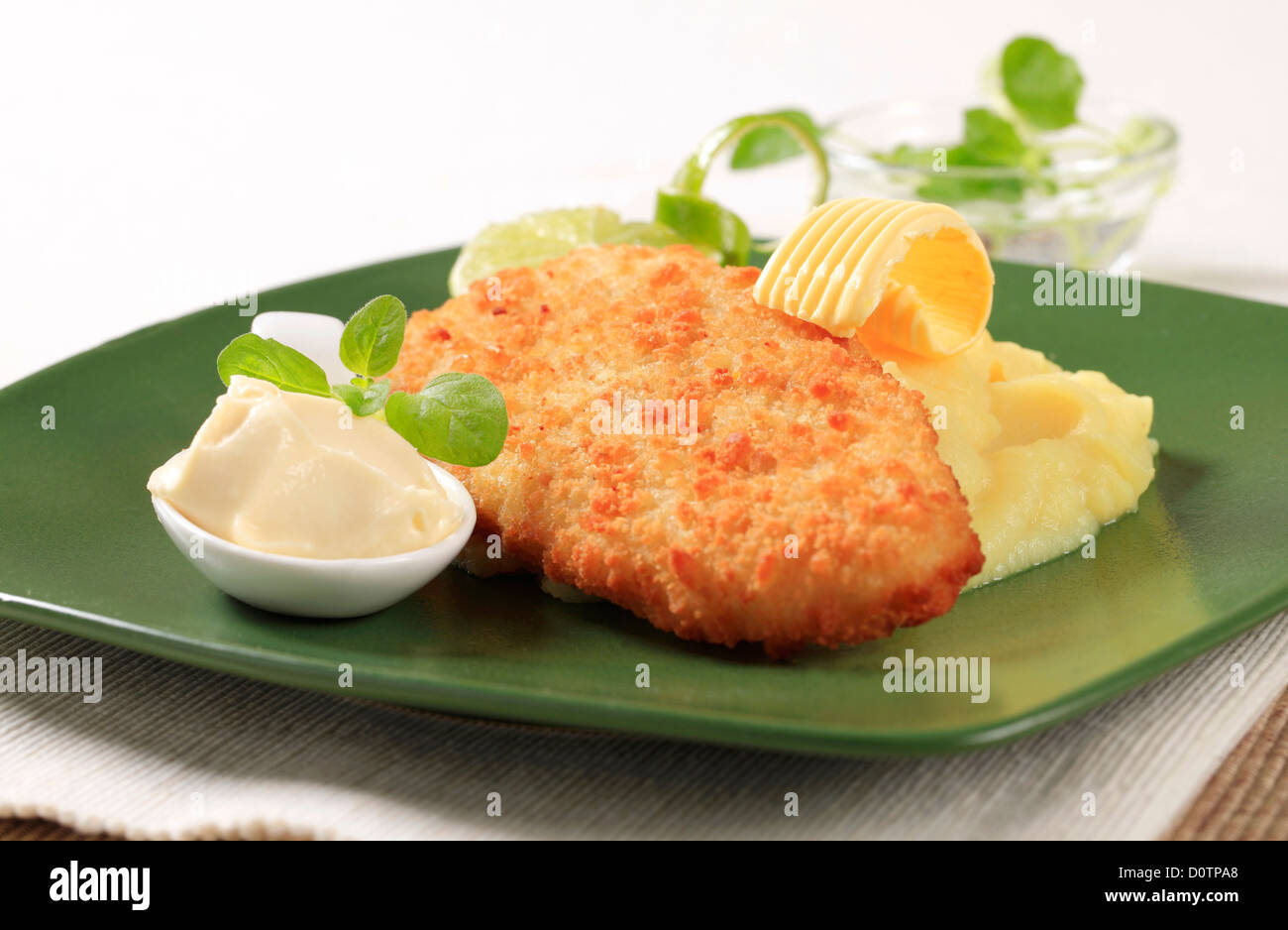 Fried breaded fish served with mashed potato - Stock Image