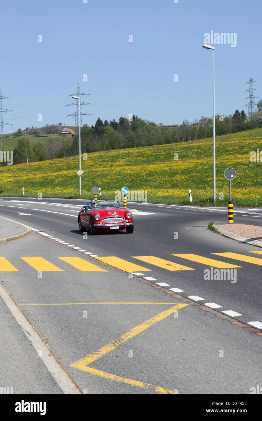 Red car on road in Switzerland Stock Photo